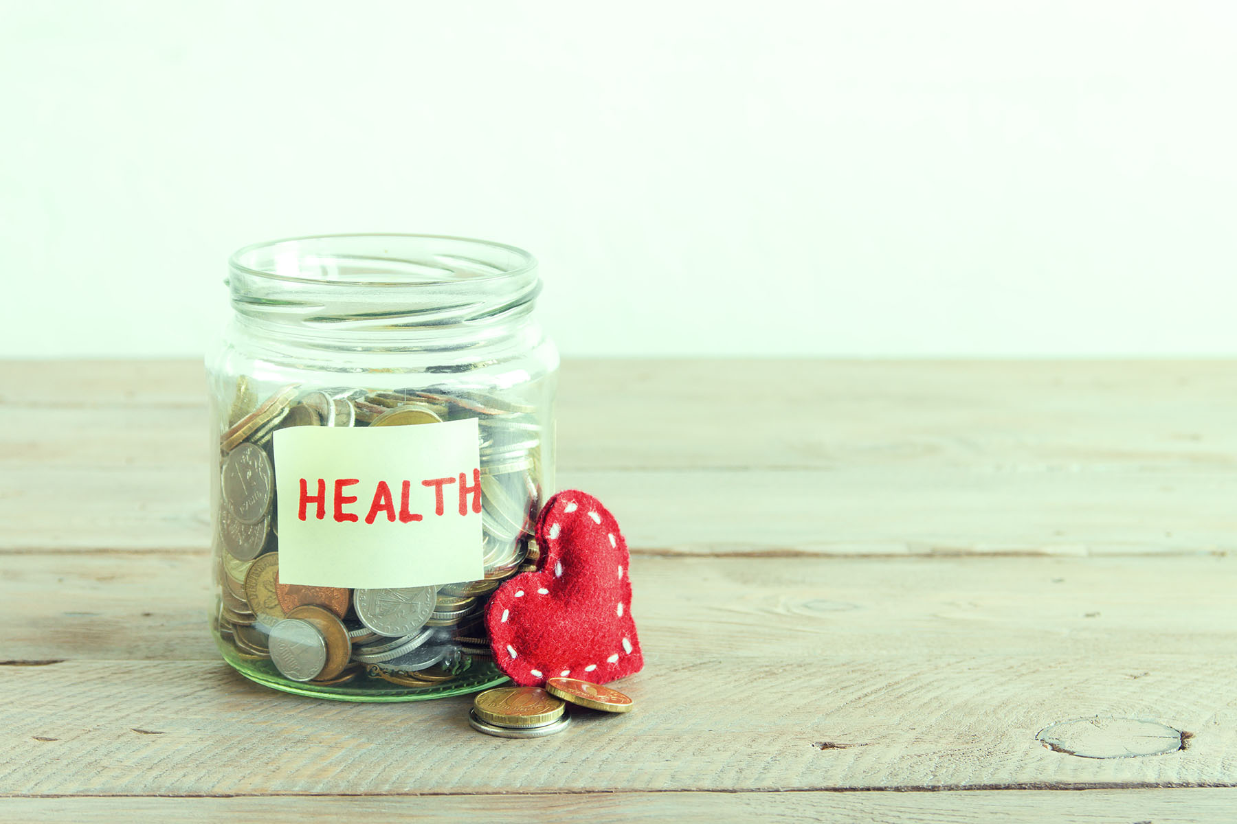Coins in glass jar with red heart and Health label. Money savings, charity and donation concept, copy space.