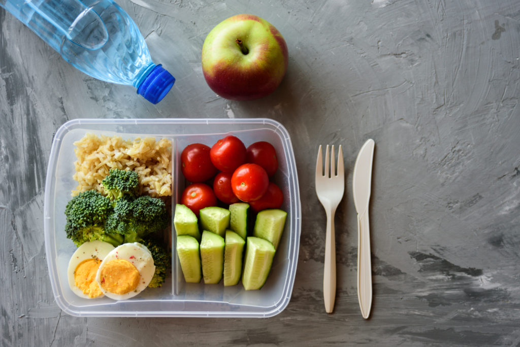 Lunch box with healthy food. Rice, broccoli, tomato, cucumber, eggs, apple and water. On grey concrete background