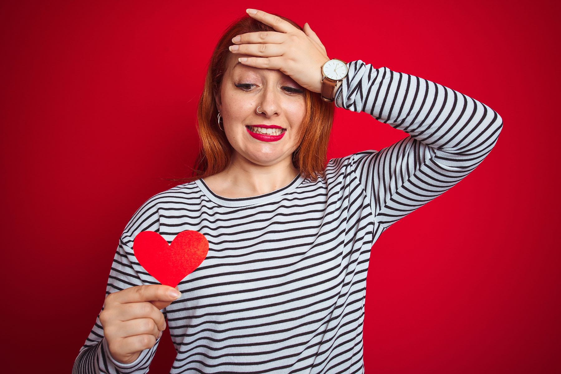 Beautiful redhead romantic woman holding heart standing over isolated red background stressed with hand on head, shocked with shame and surprise face, angry and frustrated. Fear and upset for mistake.
