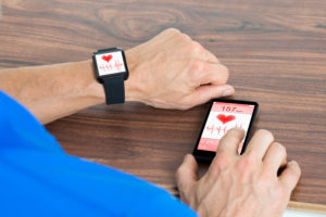 Close-up Of Male Hand With Smartwatch And Cellphone Showing Heartbeat Rate Sitting At The Table
