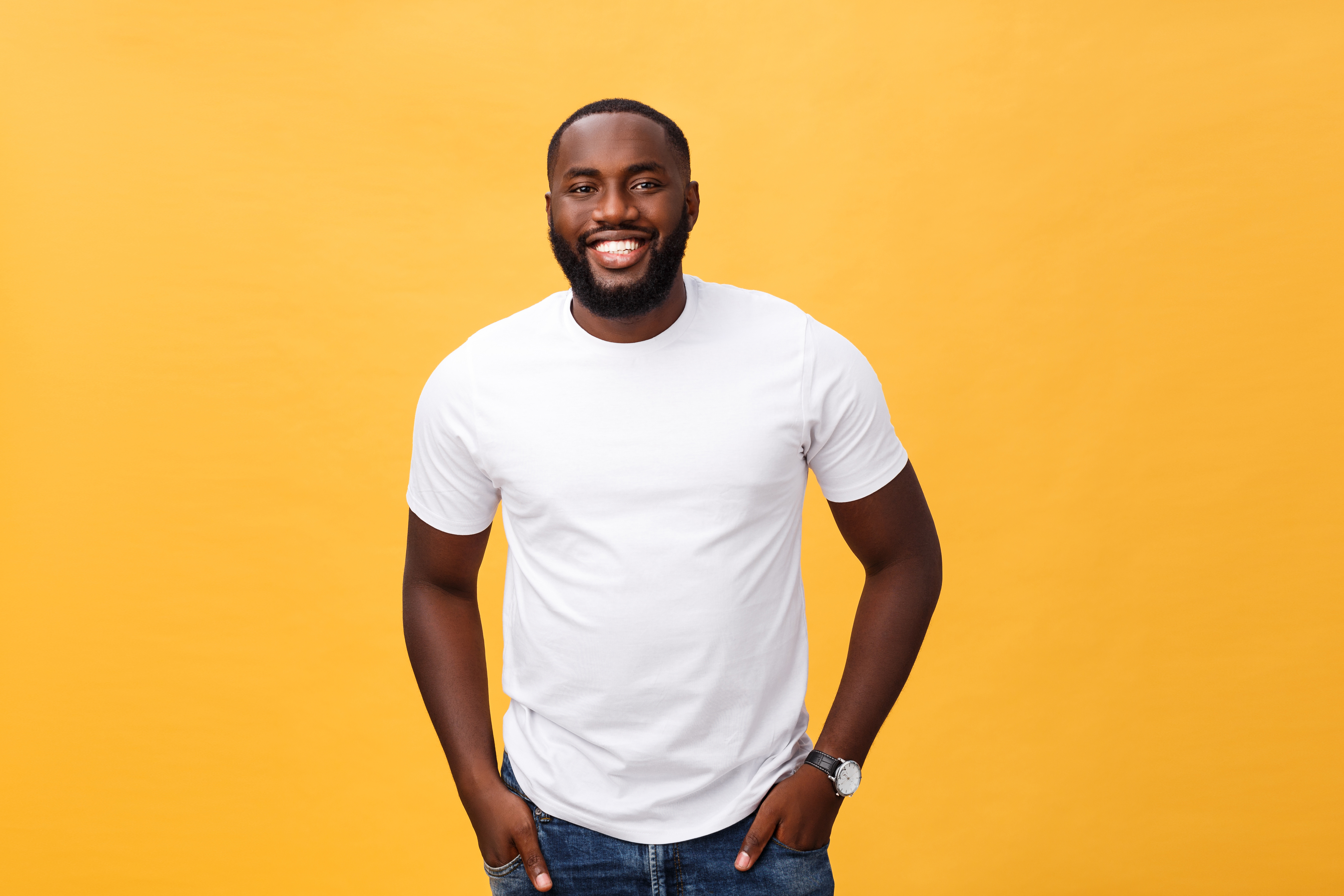 Portrait of delighted African American male with positive smile, white perfect teeth, looks happily at camera, being successful enterpreneur, wears white t shirt