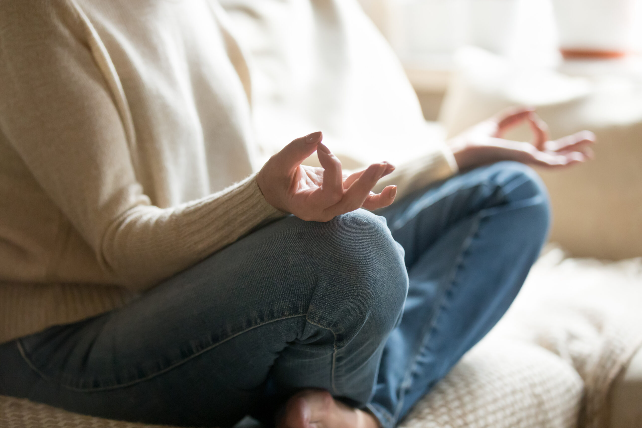 Calm senior woman sitting on sofa holding hands in mudra practicing home yoga in lotus pose for relaxation, old mature middle aged female enjoying meditating alone for peaceful mind, close up view