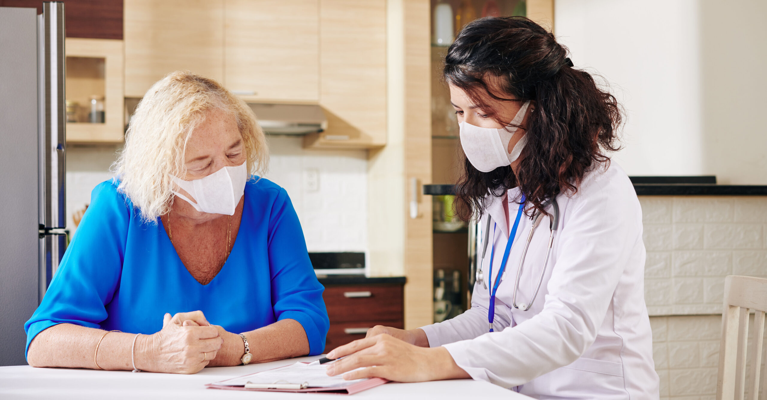 Young female doctor in medical mask showing prescription to senior patient