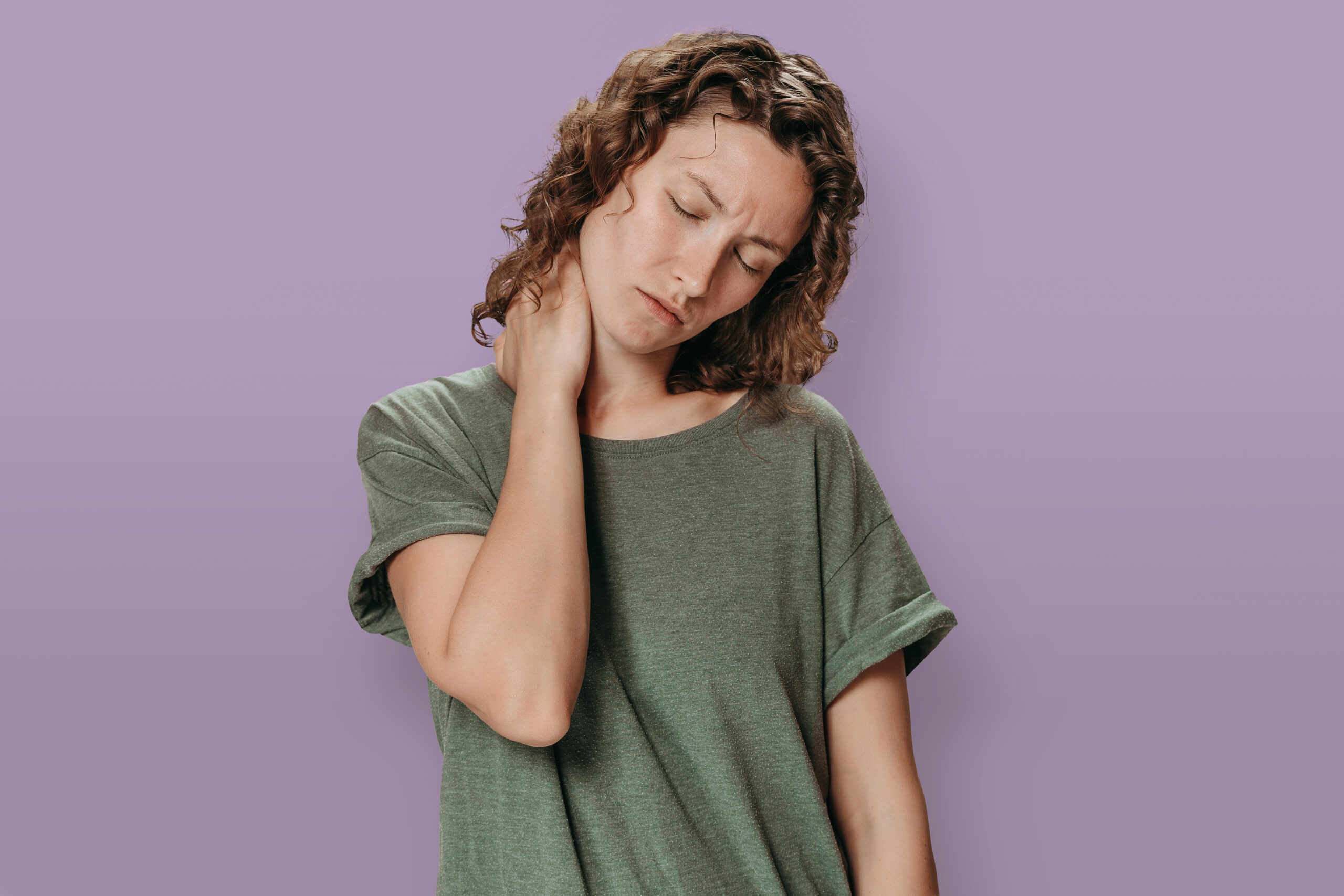 Tired young attractive woman suffering from neck pain rubbing massaging tensed muscles to decrease joint pain, isolated on violet background. Symptom of cervical chondrosis. Pain concept. Copy space