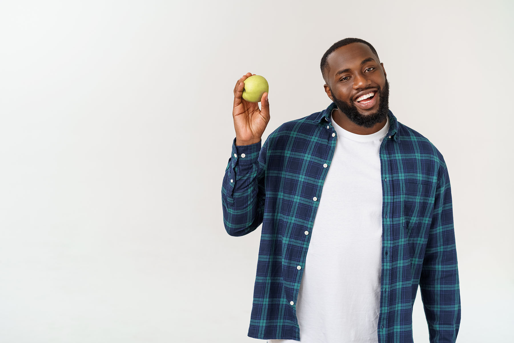 African man with green apple isolate over white background