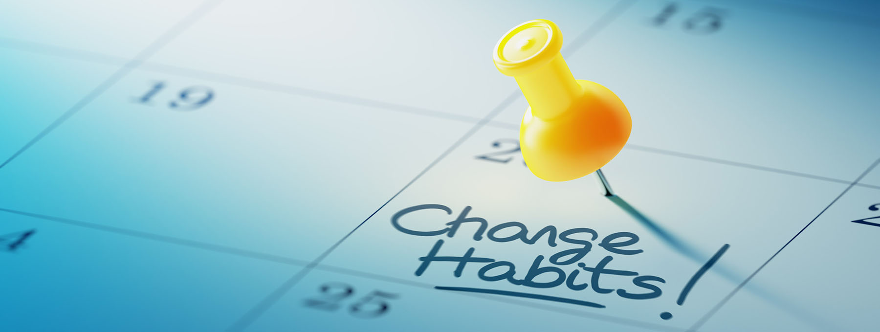 Concept image of a Calendar with a yellow push pin. Closeup shot of a thumbtack attached. The words Change Habits written on a white notebook to remind you an important appointment.