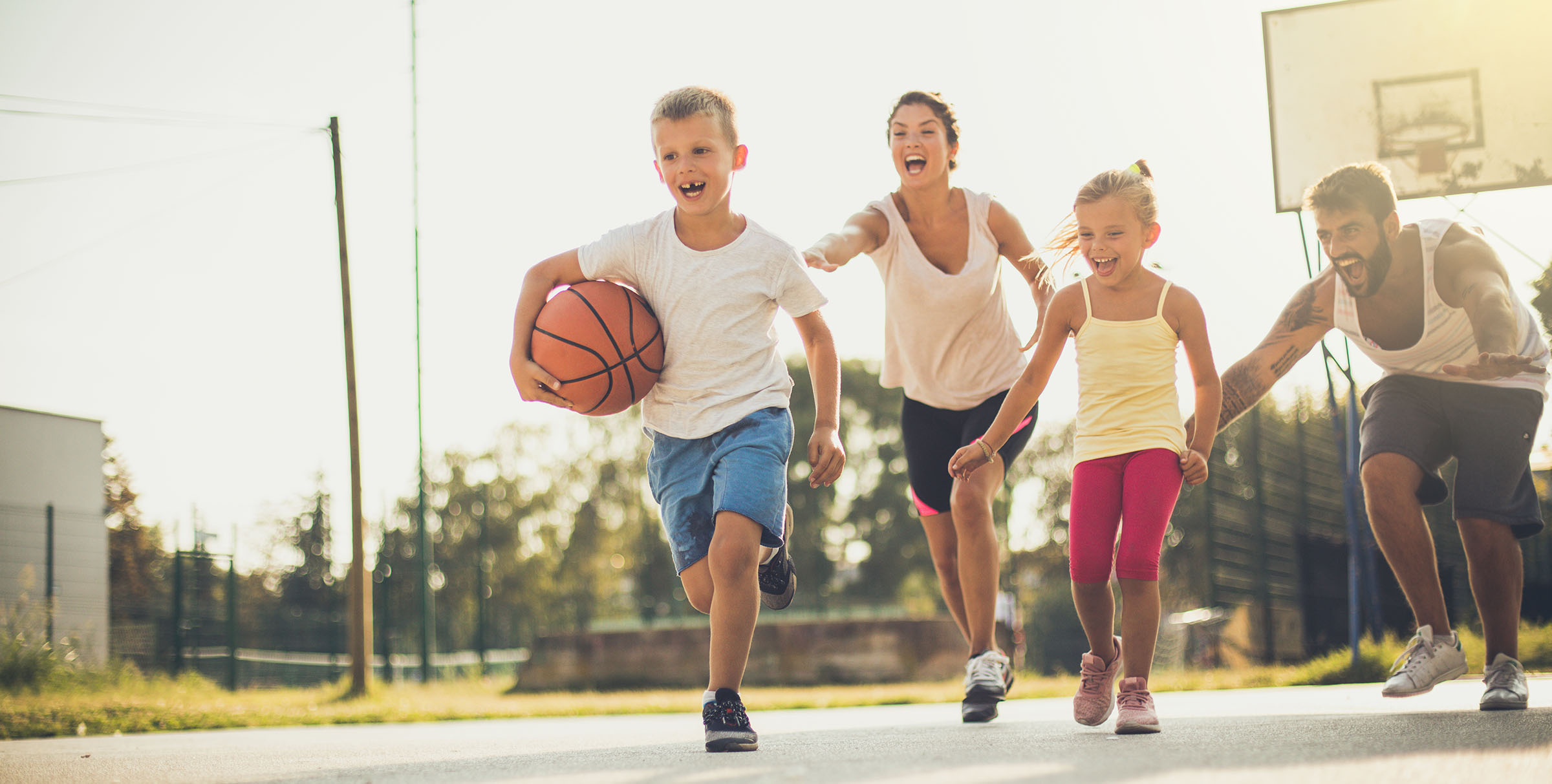 Spring is great for family sport.  Happy family playing basketball outside. On the move.