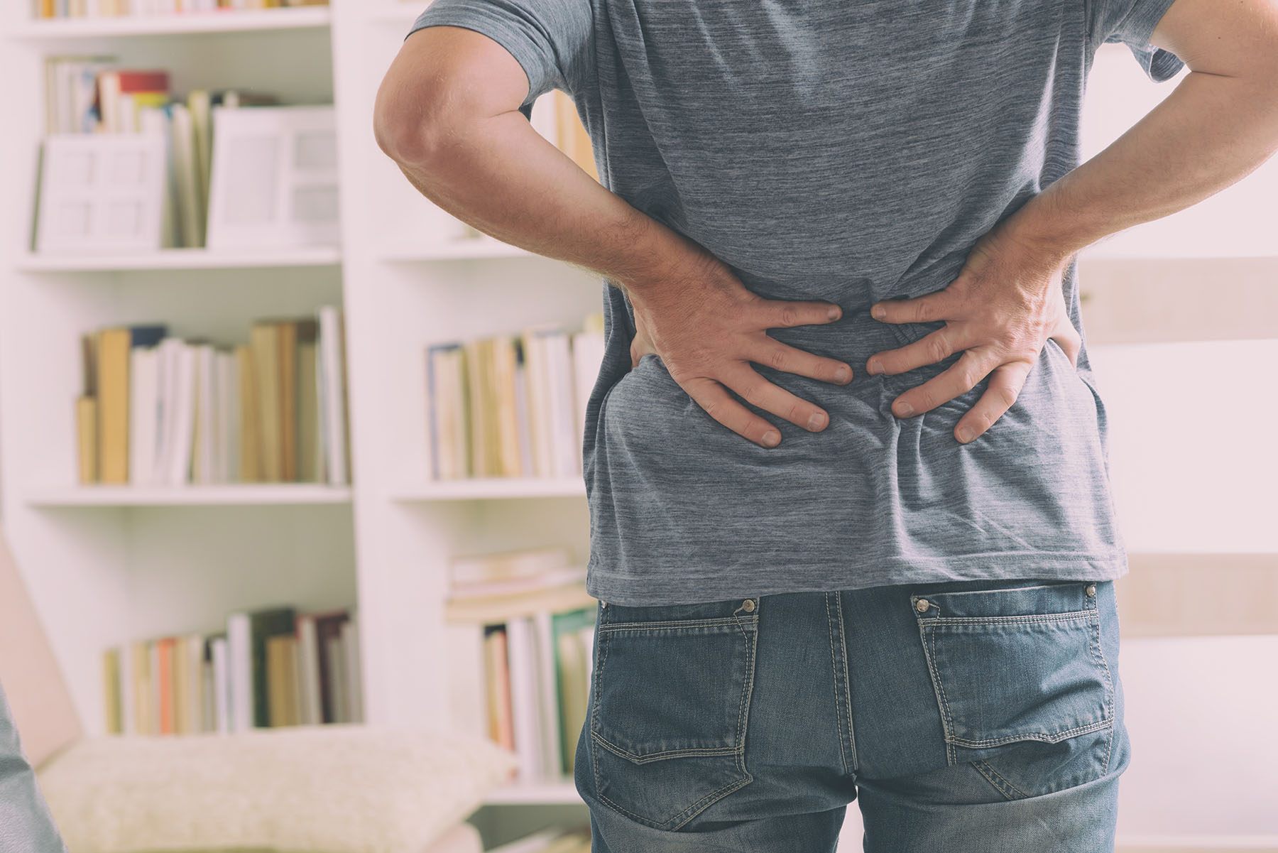 Man in home office suffering from low back pain standing
