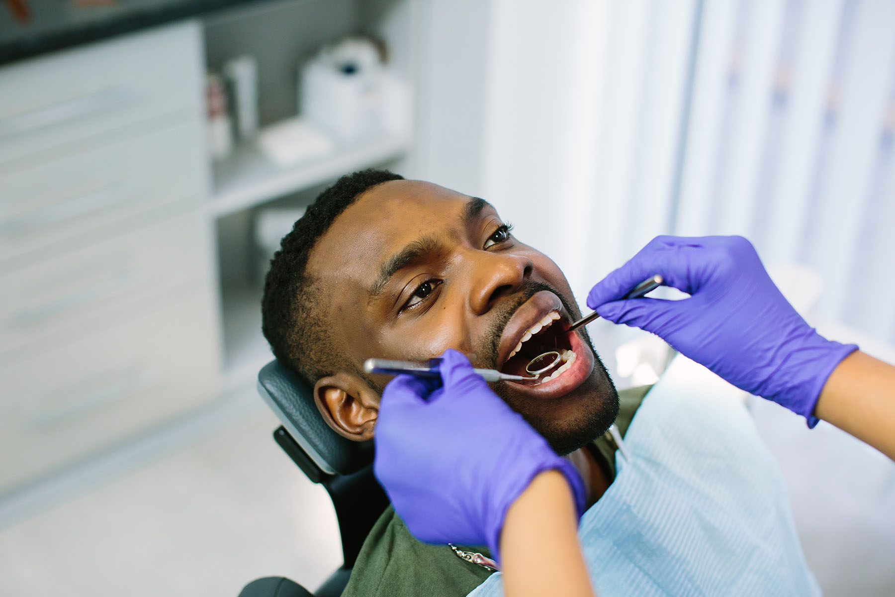 High angle view of male african american patient being examined by dentist in clinic