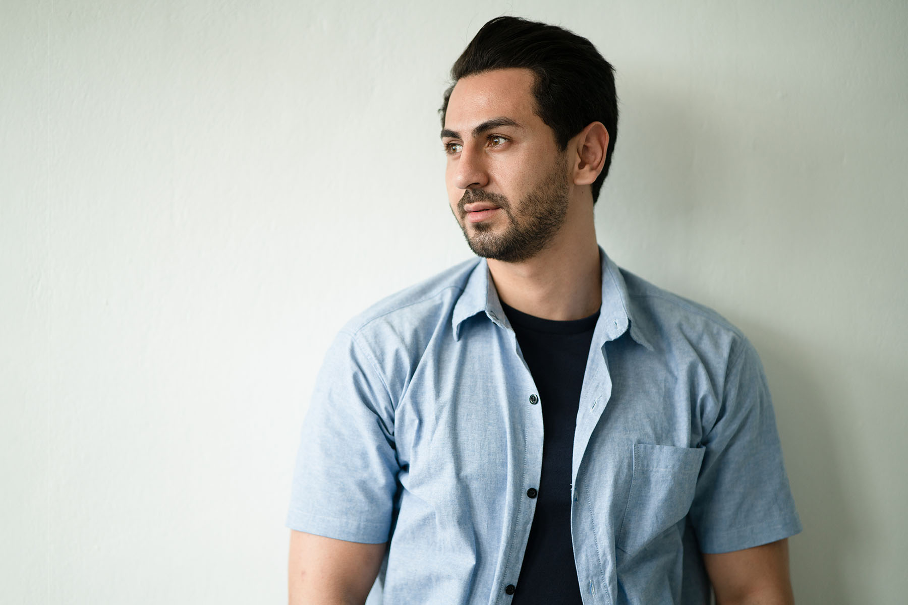 A panoramic portrait of a handsome Hispanic Arabian ethnic wearing casual blue shirt looks sideways, has a serious expression in front of the camera standing before the white wall with copy space.