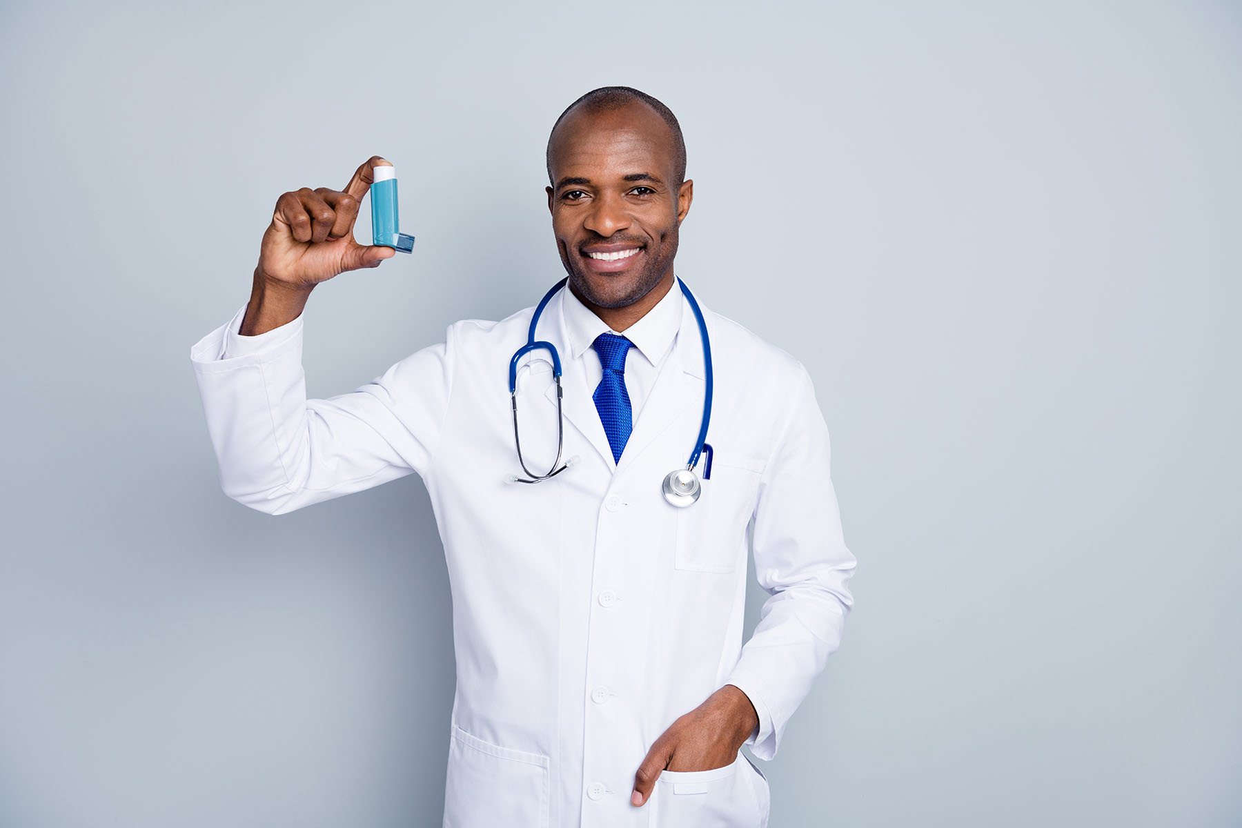 Photo of family doc dark skin guy hold inhaler asthma attack advising, medical prescription against self-treatment concept wear stethoscope lab coat isolated grey color background