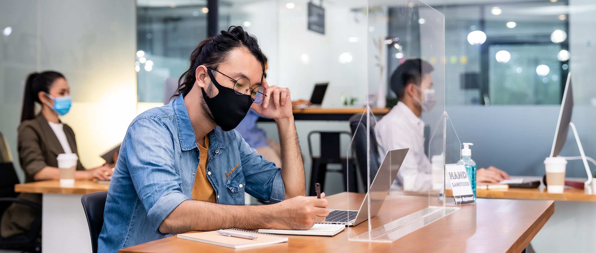 Panoramic group of business worker team wear protective face mask in new normal office with social distance practice with hand sanitiser alcohol gel on table prevent coronavirus COVID-19 spreading