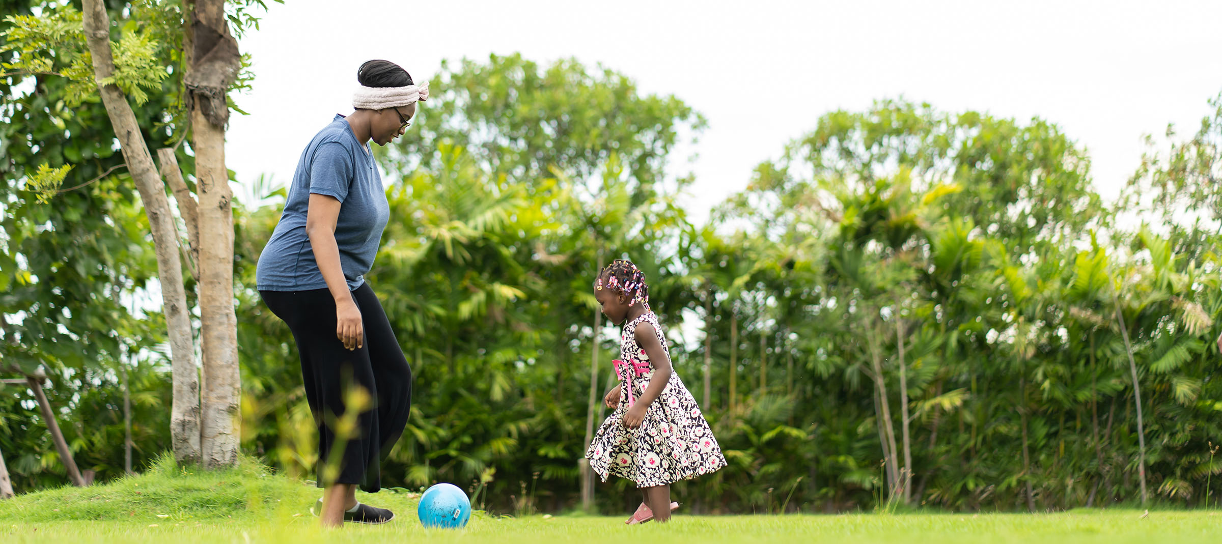 African American cute girl playing with black mother outdoors at home. happy family in holiday concept.