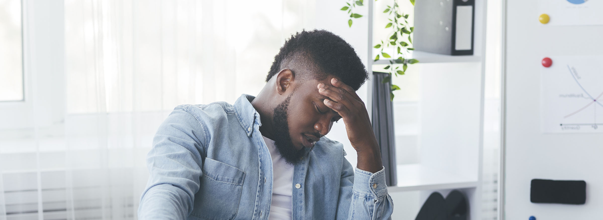 Business problems. Depressed black businessman drinking alcohol at workplace in office, having financial issues.