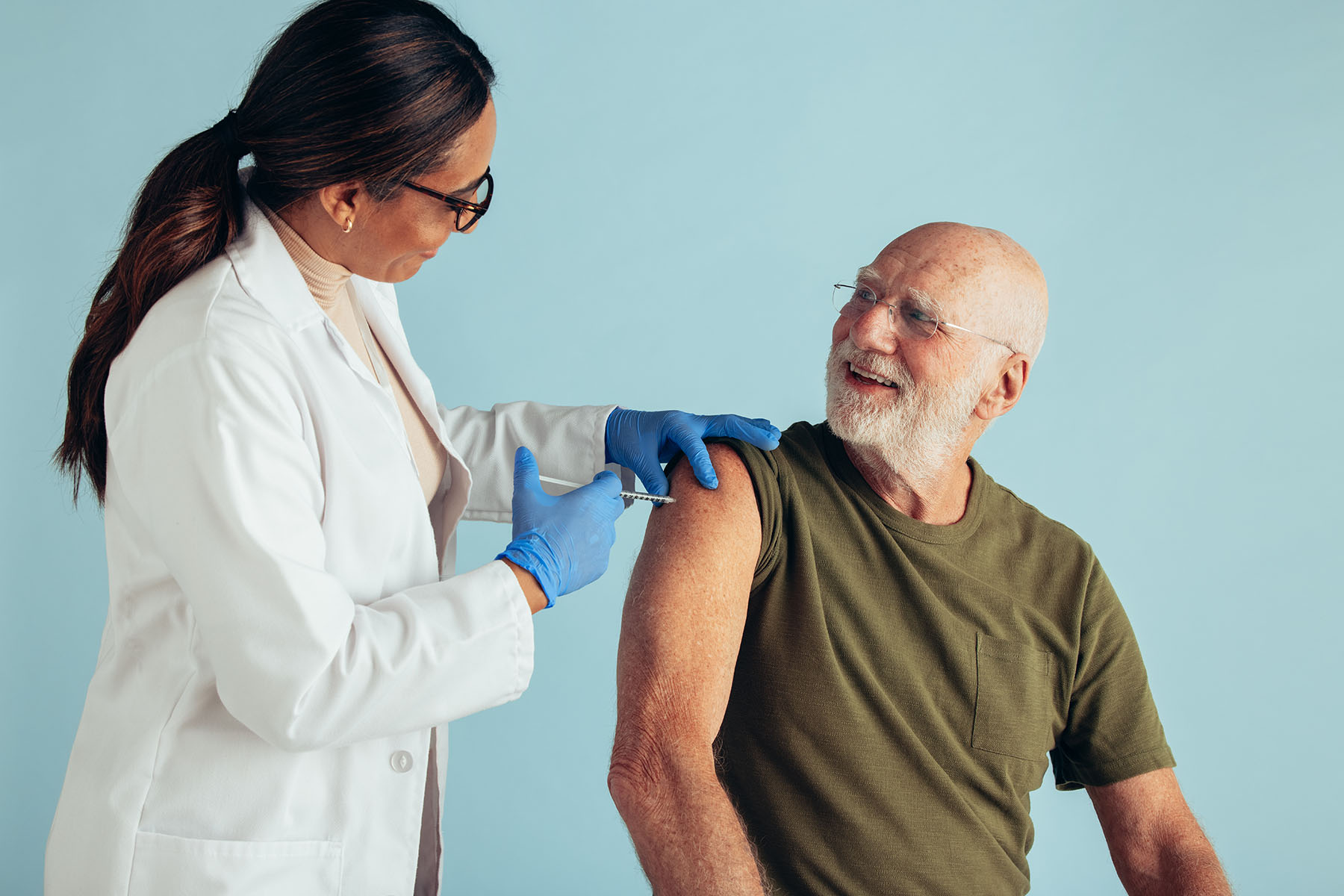 Senior man getting vaccine dose from a doctor. Doctor giving vaccine to a senior man on blue background.