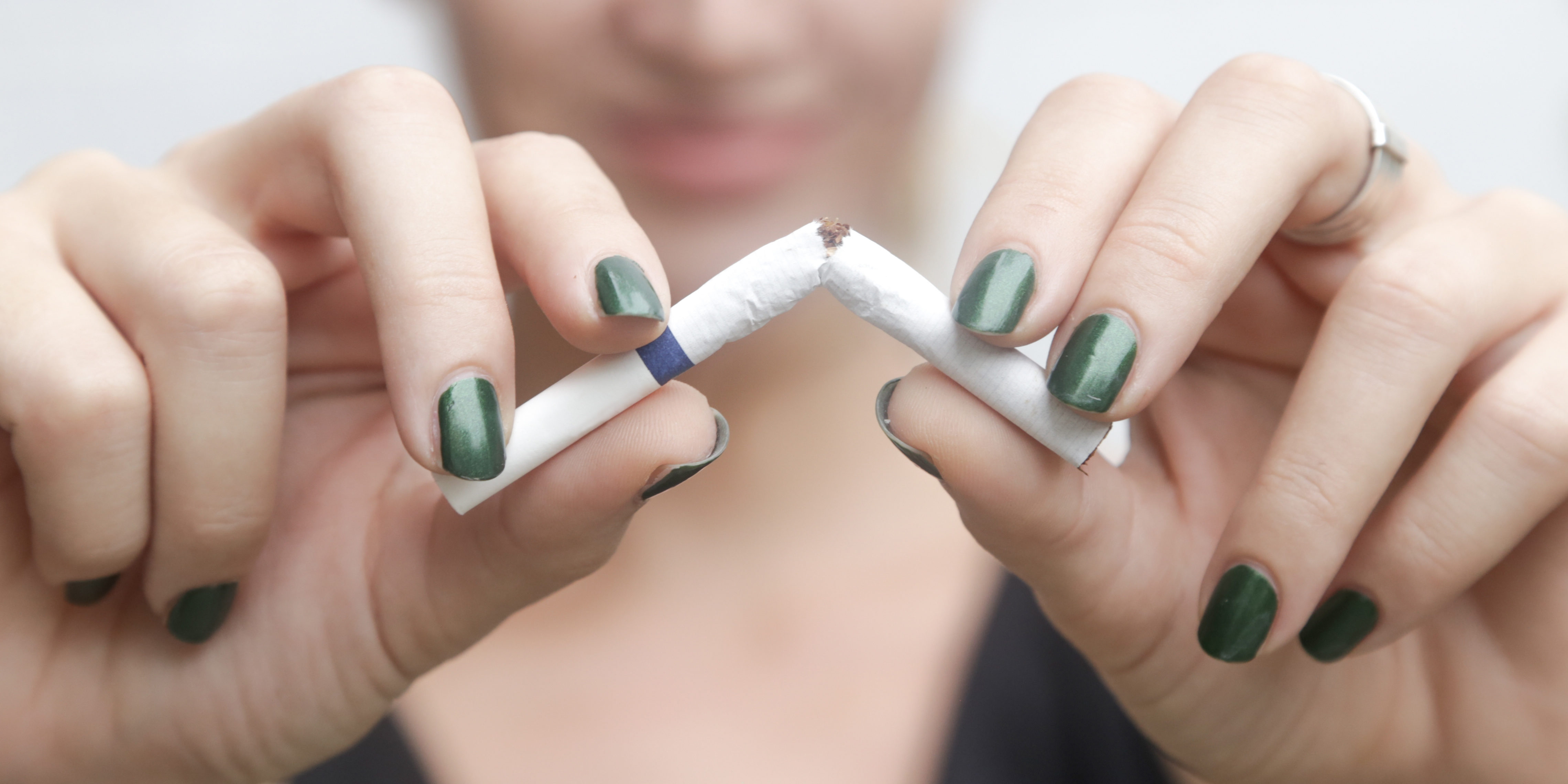 Young woman breaking down cigarette to pieces. - quit smoking concept