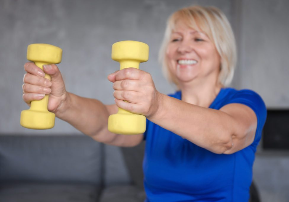 Mature woman training with dumbbells at home