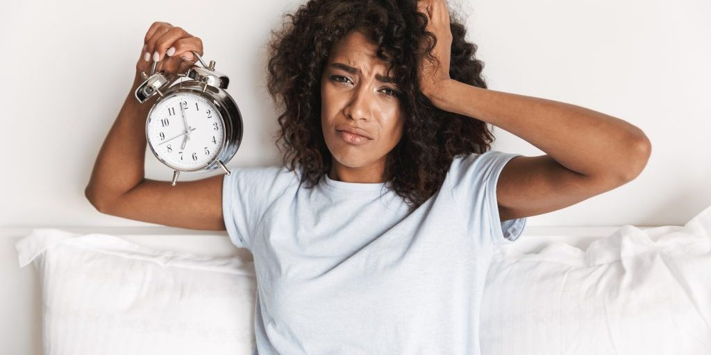 Upset young african woman showing alarm clock while sitting in bed in the morning