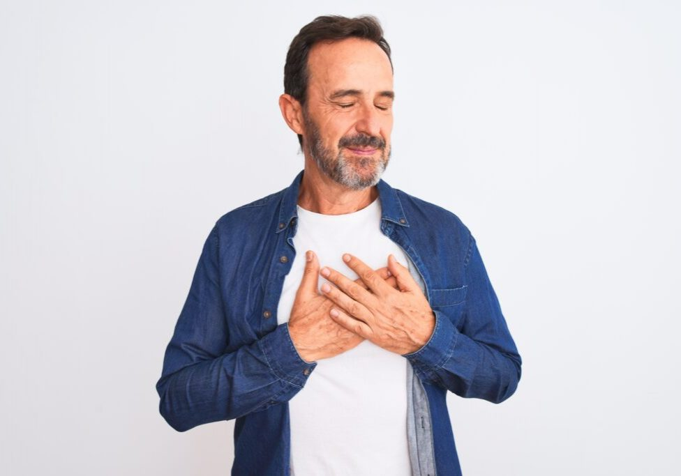 Middle age handsome man wearing blue denim shirt standing over isolated white background smiling with hands on chest with closed eyes and grateful gesture on face. Health concept.