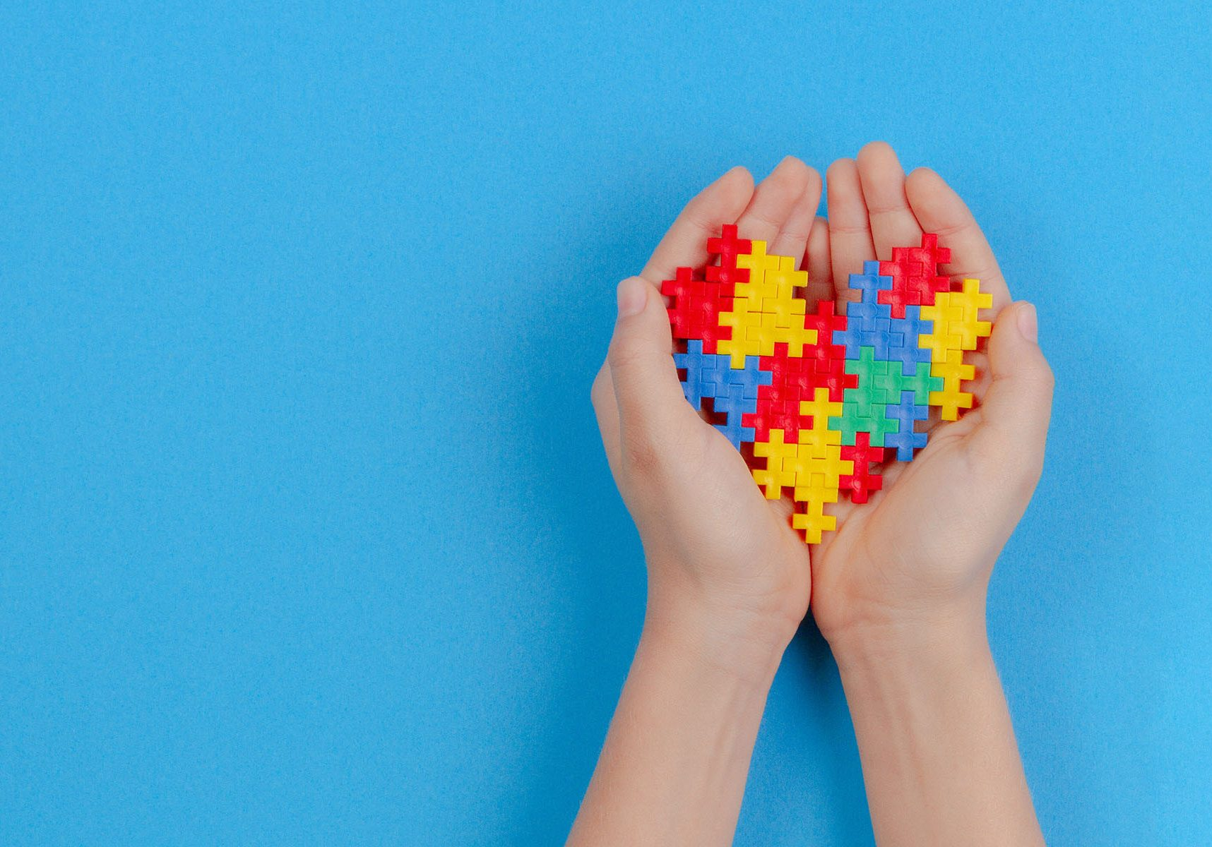 Kid hand holding colorful heart on blue background. World autism awareness day concept.