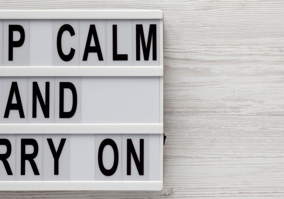'Keep calm and carry on' words on a lightbox on a white wooden background, top view. Overhead, from above, flat lay. Copy space.