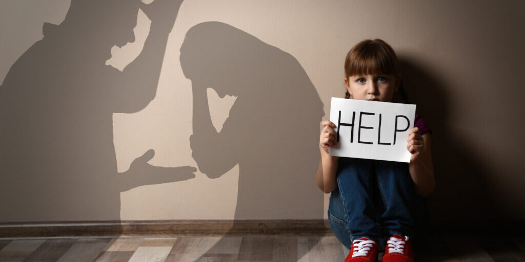 Sad little girl with sign HELP sitting on floor and silhouettes of arguing parents